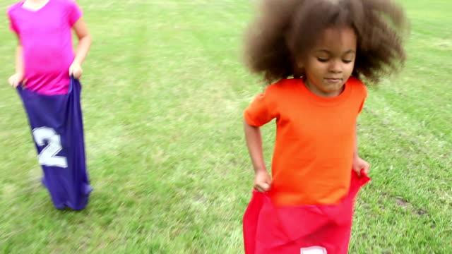 multi-ethnic children in potato sack race - sack race stock videos & royalty-free footage