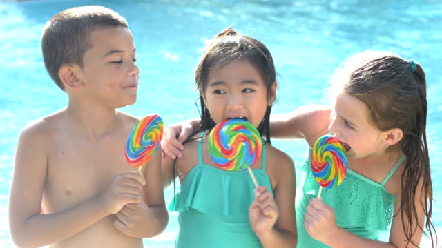 vídeos de stock e filmes b-roll de multi-ethnic children licking lollipops by swimming pool - 6 7 years
