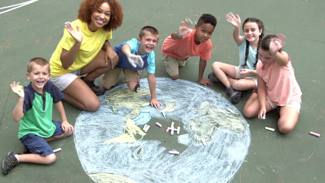 multi-ethnic children making chalk drawing of earth - primary age child stock videos and b-roll footage