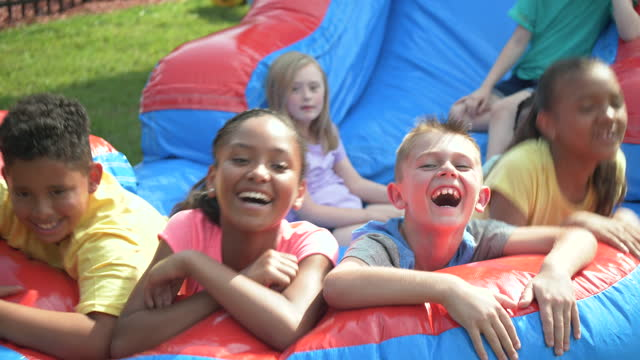 multi-ethnic children on giant inflatable slide - 8 9 years stock videos & royalty-free footage