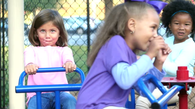 multi-ethnic children on merry-go-round making faces - etnia video stock e b–roll