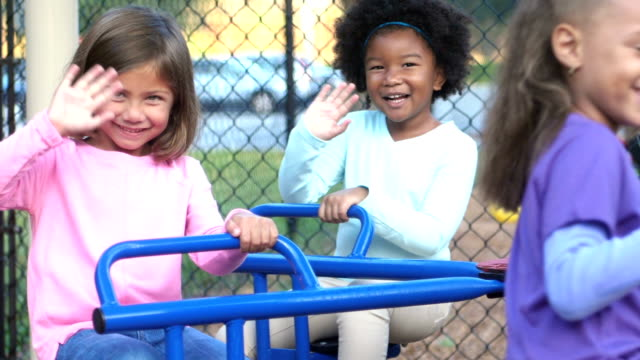 Multi-ethnic children on merry-go-round waving