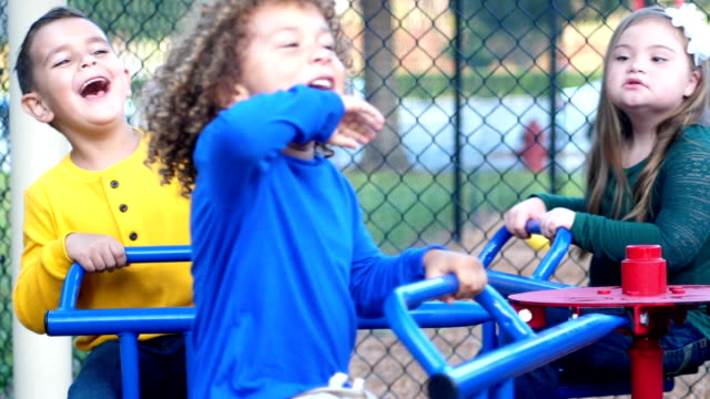 multi-ethnic children on playground merry-go-round - playground stock videos & royalty-free footage