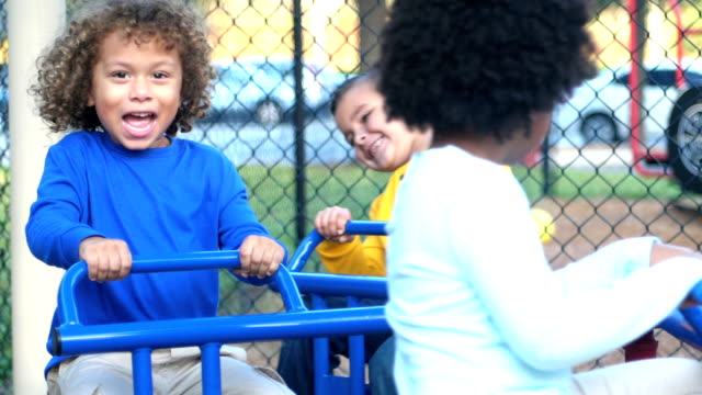Multi-ethnic children on playground merry-go-round