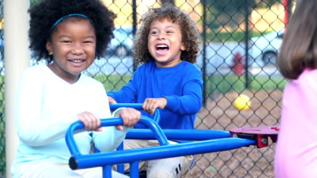 vídeos de stock, filmes e b-roll de multi-étnica crianças carrossel infantil - pátio de escola