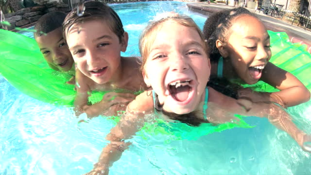 multi-ethnic children on pool raft smiling at camera - 6 7 years stock videos & royalty-free footage