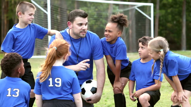 Multi-ethnic children on soccer team listening to coach