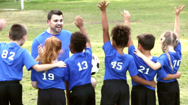 multi-ethnic children on soccer team with coach - teacher stock videos and b-roll footage
