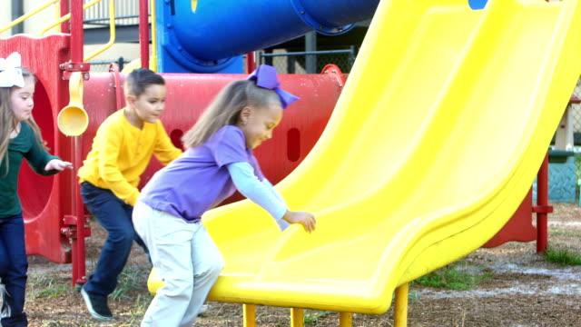 multi-ethnic  children sit on playground slide - playground stock videos & royalty-free footage