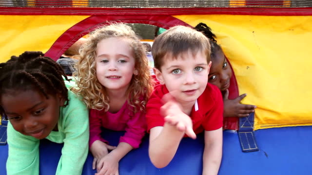 Multi-ethnic children sticking heads out bouncy castle
