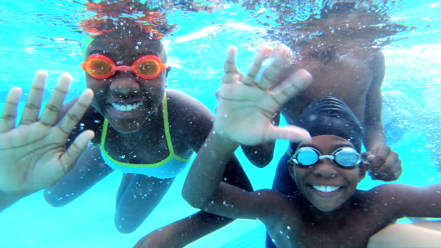 multi-ethnic children underwater waving at camera - swimming goggles stock videos & royalty-free footage