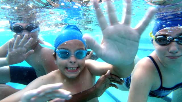 multi-ethnic children underwater waving at camera - underwater camera stock videos & royalty-free footage