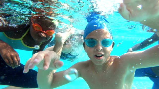 Multi-ethnic children underwater waving at camera