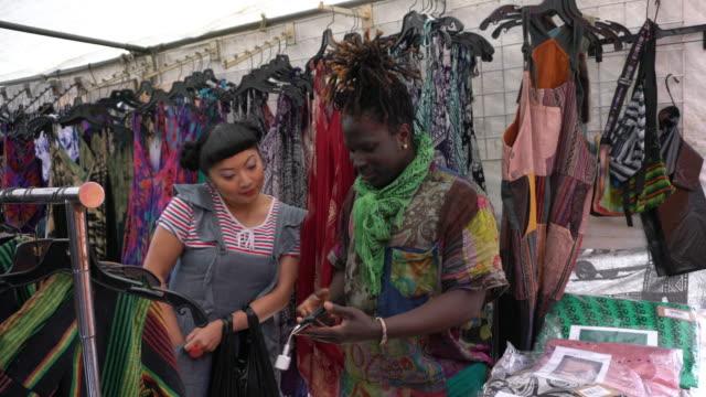 vídeos de stock e filmes b-roll de multi-ethnic client and vendor small business service street vendor - pequeno