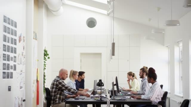 vidéos et rushes de des collègues multi-ethniques utilisant des ordinateurs au bureau - entrepreneur