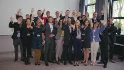 Multi-ethnic colleagues waving in auditorium