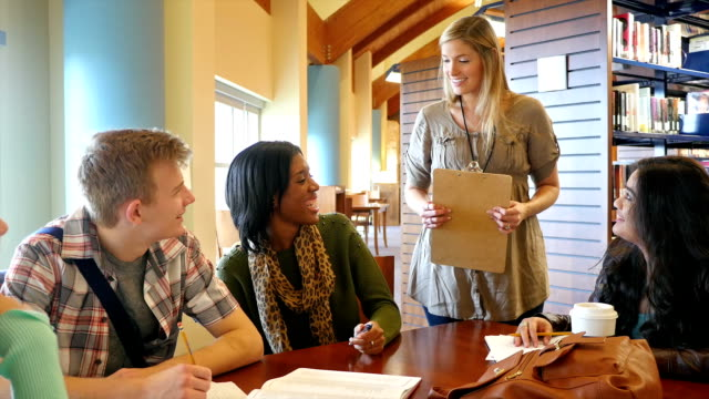 Multi-ethnic college study group studies for exam together in college library