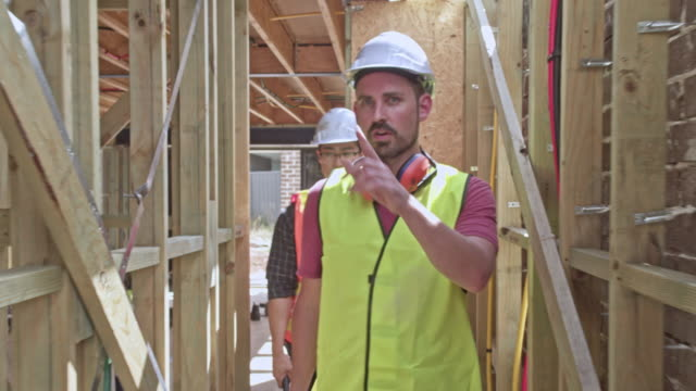 multi-ethnic construction workers talking at construction site - construction site stock videos and b-roll footage
