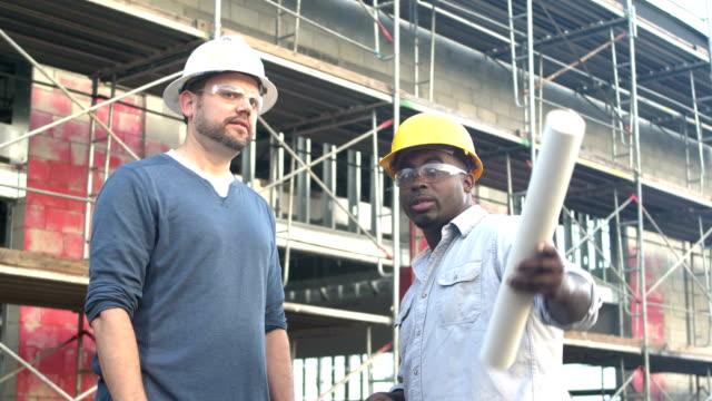 multiethnische bauarbeiter im gespräch auf der baustelle - gewalt stock-videos und b-roll-filmmaterial
