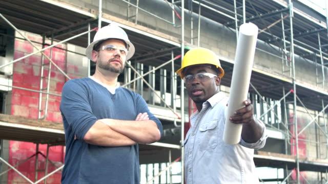 multiethnische bauarbeiter im gespräch auf der baustelle - grundriss stock-videos und b-roll-filmmaterial
