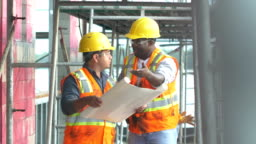 Multi-ethnic construction workers talking at job site
