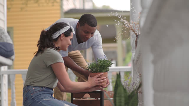 a multi-ethnic couple arrange potted plants on their front porch - decoration stock videos & royalty-free footage