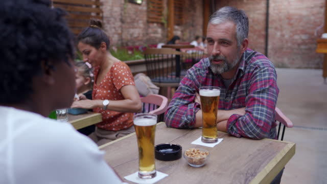 multi-ethnic couple drinking beer and enjoying weekend at outdoor pub - mid adult couple stock videos & royalty-free footage