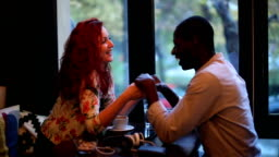 Multi-ethnic couple flirting and holding hands