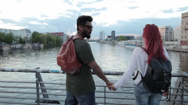 Multi-ethnic couple holding hands, looking out at view of Berlin on bridge over Spree river