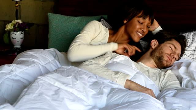 multi-ethnic couple in bed waking up - toccare con un dito video stock e b–roll