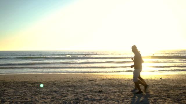 multi-ethnic couple jogging at beach against sky - full length点の映像素材/bロール