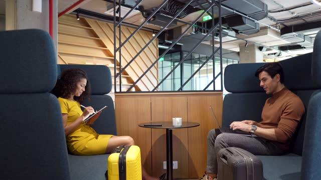 vídeos de stock, filmes e b-roll de casal multiétnico de pessoas de negócios sentados em uma área isolada e usando dispositivos móveis - área de embarque de aeroporto