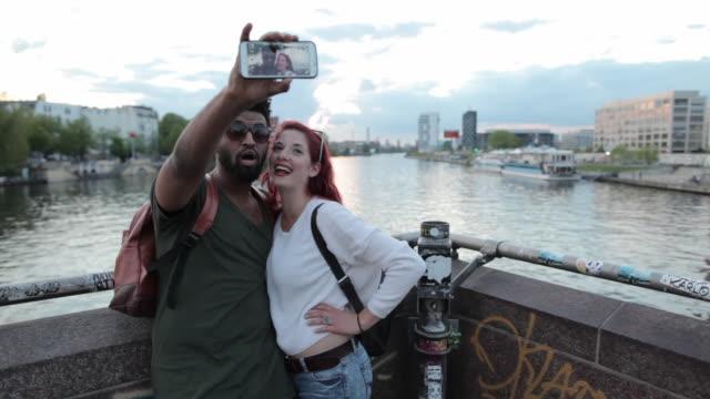 Multi-ethnic couple taking selfie on bridge over Spree river in Berlin, Germany