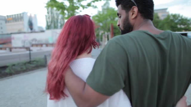 Multi-ethnic couple walking around Berlin, Germany, talking