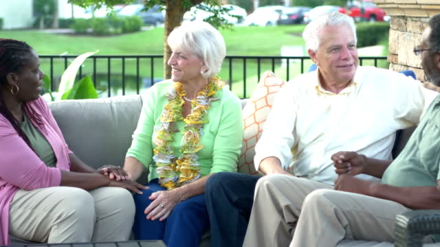 stockvideo's en b-roll-footage met multi-etnische paren zittend op patio converseren - 70 79 jaar