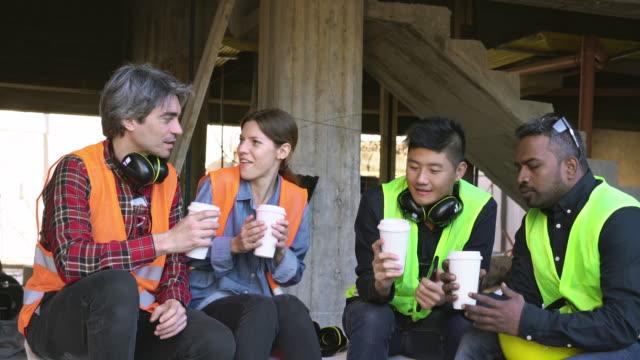 建設現場で座ってコーヒーを共有する多民族の同僚 - resting点の映像素材/bロール
