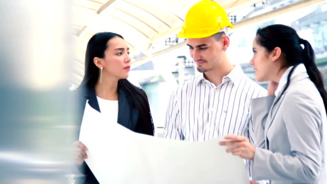 Multiethnic diverse group of engineers or business partners at construction site, working together on building's blueprint, architect industry or teamwork concept.