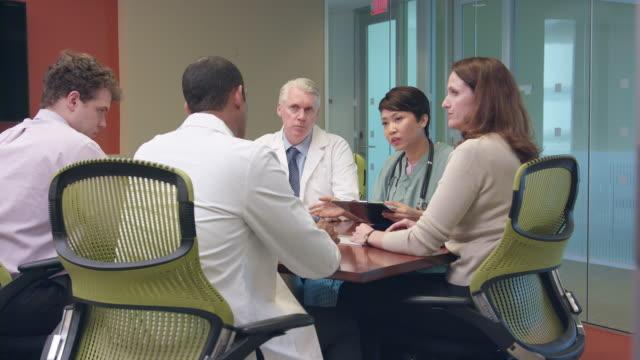 vídeos de stock e filmes b-roll de multi-ethnic doctors meet in modern office - ws - empregado