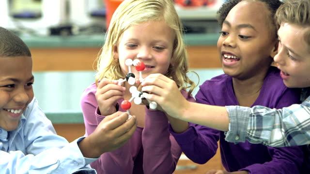 Multi-ethnic elementary school children in science class