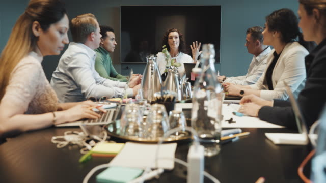 multi-ethnic executives listening to businesswoman brainstorming during meeting in board room at creative office - medium group of people stock videos & royalty-free footage