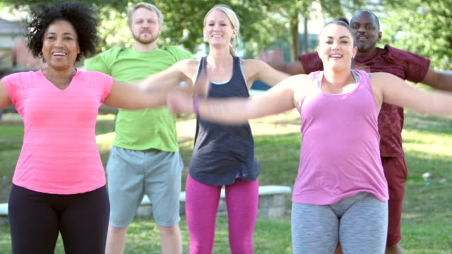 multi-ethnic exercise class, jumping jacks in park - star jump stock videos & royalty-free footage