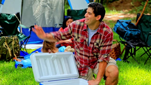 multi-ethnic family camping outdoors in tent. - cooler container stock videos and b-roll footage
