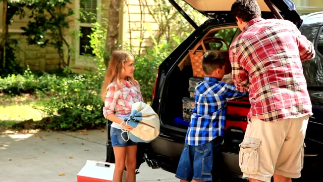 multi-ethnic family pack car for vacation or road trip. - bagaglio video stock e b–roll