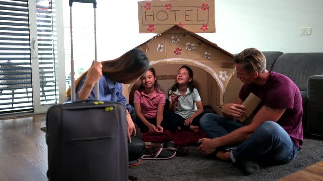 vídeos de stock, filmes e b-roll de família multiétnica brincando com hotel de papelão em casa - caixa de papelão