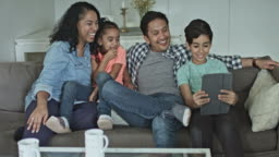 Multi-ethnic family taking selfie on digital tablet