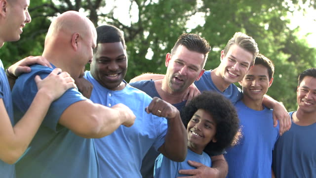 Multi-ethnic fathers and sons in blue, fist bump