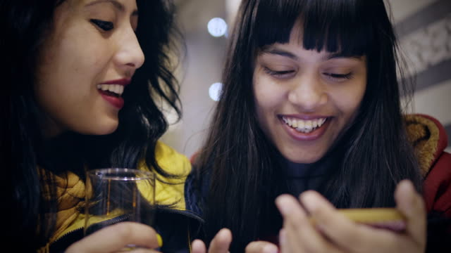 multi-ethnic female friends sharing smartphone together. - india video stock e b–roll