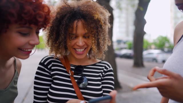 vidéos et rushes de amis féminins multiethniques restant sur le trottoir, regardant le téléphone intelligent et commérages - t shirt