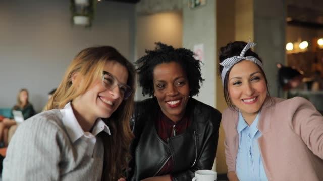 Multi-ethnic female friends taking selfie in cafe