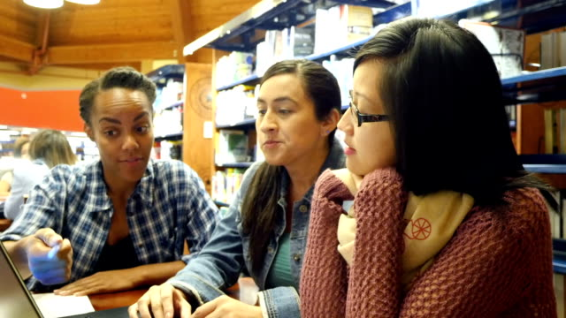 Multi-ethnic friends brainstorm and study in college library